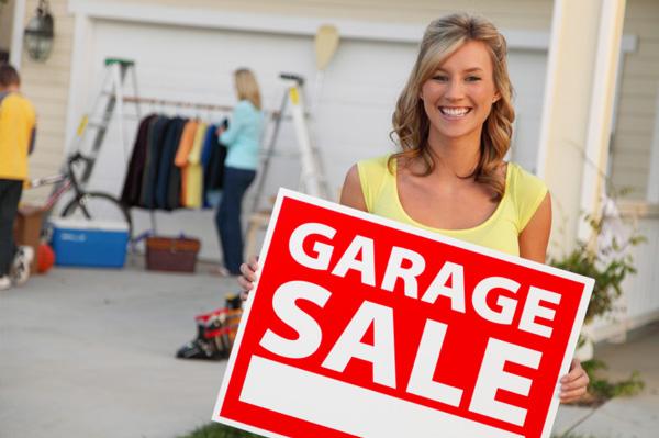 woman-having-garage-sale-holding-sign